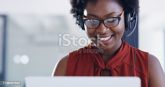 Shot of young woman using a laptop and headset in a modern office