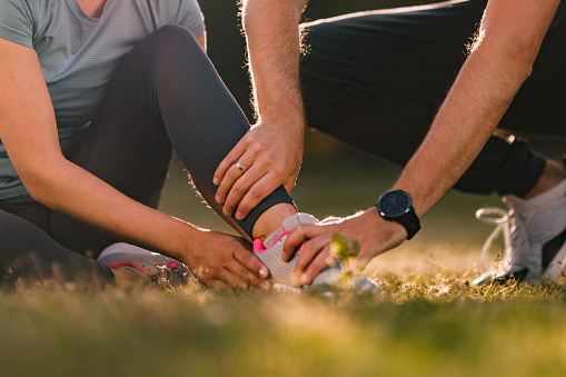 Close up of unrecognizable man assisting his wife with ankle pain during sports training in nature. Copy space.