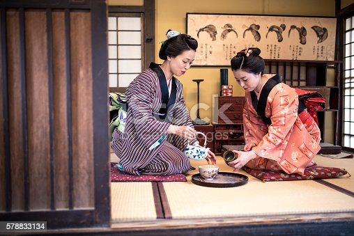Two Japanese women wearing a kimono drinking tea indoors, in tea room. They are talking and having fun.