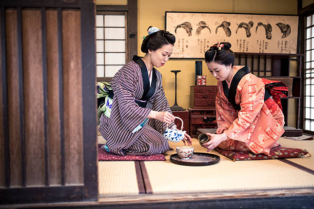 Let me pour you tome tea Two Japanese women wearing a kimono drinking tea indoors, in tea room. They are talking and having fun. tea room stock pictures, royalty-free photos & images