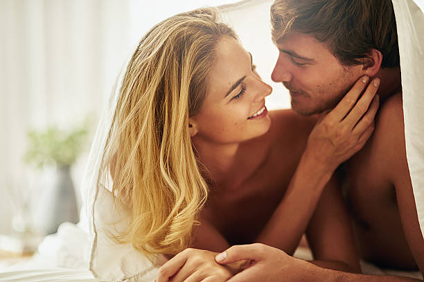 Let me see this handsome face Cropped shot of an affectionate young couple relaxing at home real couples making love stock pictures, royalty-free photos & images