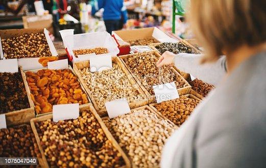 Beautiful blonde woman buying walnuts at food market.