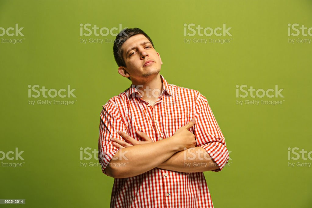 Let me think. Doubtful pensive man with thoughtful expression making choice against green background - Royalty-free Adult Stock Photo