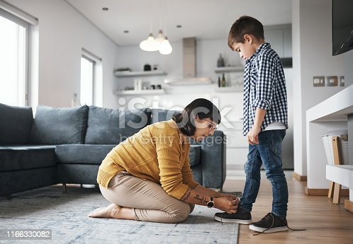Shot of a mother tying her son's shoelaces at home