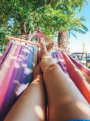 Feet of a young caucasian woman in hammock on the beach.