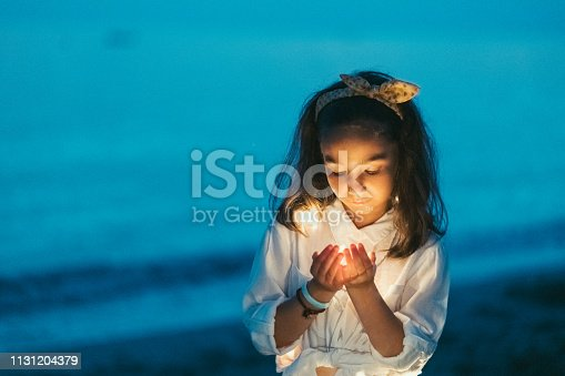 Little girl holding lights in hands cupped and making a wish at night