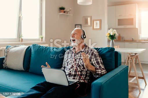 Happy senior man using laptop and headphones while listening to his favorite music on the internet at home in the living room