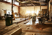 Still life shot of the machinery and piles of wood inside a carpentry workshop