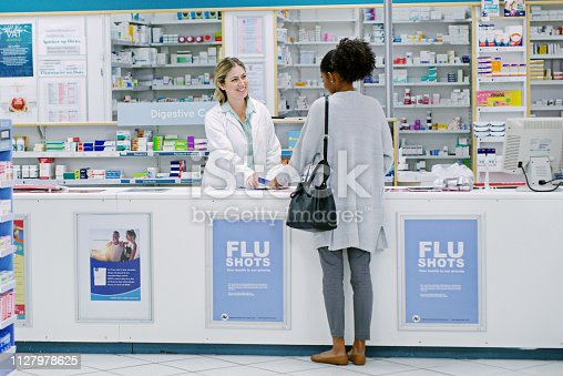 Rearview shot of a young woman purchasing over the counter medication from a female pharmacist