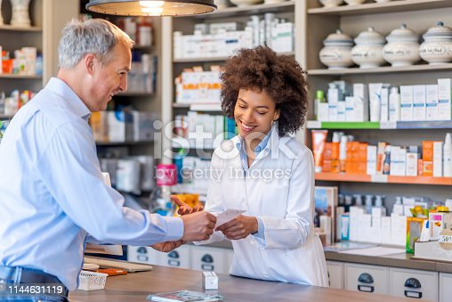 Photo of female mixed race Pharmacist giving prescriptions of medicine to mature gray hair customer in pharmacy. Female pharmacist showing medicine to male customer in pharmacy. Chemist suggesting medical drug to buyer in pharmacy drugstore.