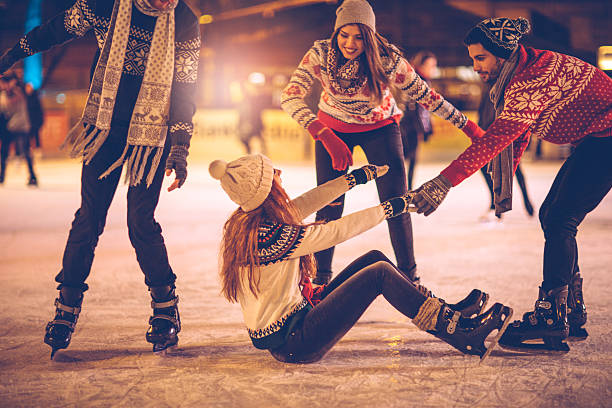 Let us help you Friends having so much fun while ice skating.  Wearing warm clothing. City is decorated with christmas lights. ice skating stock pictures, royalty-free photos & images