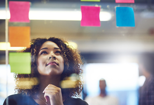 Shot of a young woman having a brainstorming session with sticky notes at work