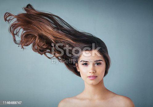 Studio portrait of a beautiful young woman posing against a gray background