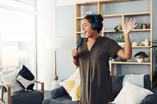 Shot of a happy young woman singing with a microphone in the living room at home