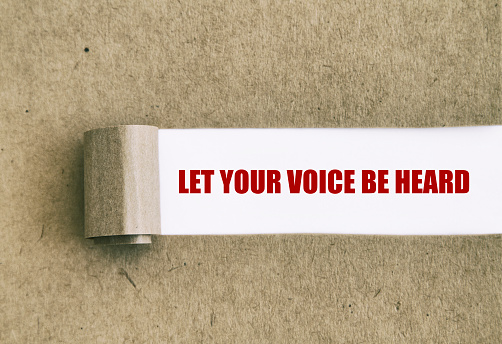 Let your voice be heard written under torn paper.