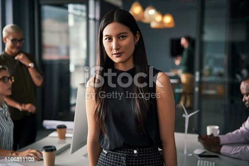 Portrait of an attractive young businesswoman standing inside an office with her colleagues working in the background