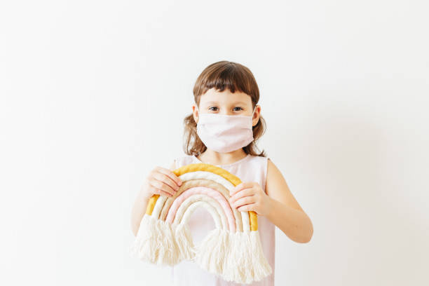 lasst uns alle gut sein. Kind zu Hause tragen wiederverwendbare Textilmaske halten Textil handgefertigten Regenbogen. – Foto