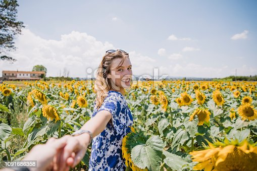 Point of view shot of a young woman grabbing her partners hand to go and explore a sunflower field in Italy.