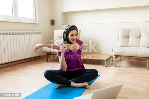 An Arabian young woman is practicing yoga in the bedroom. A Muslim woman is looking at a video lesson of yoga on her laptop and exercising at home.