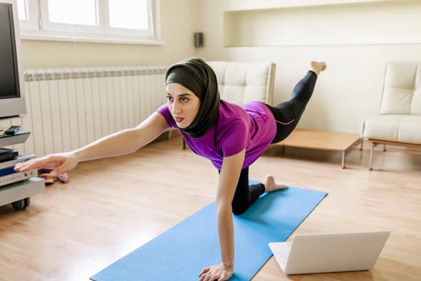 Let's Burn That Belly Fat Avec une séance d'entraînement à domicile. Une femme musulmane fait du yoga à la maison avec de l'aide en ligne - Photo