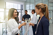 Shot of a businesswomen toasting with champagne in a modern office