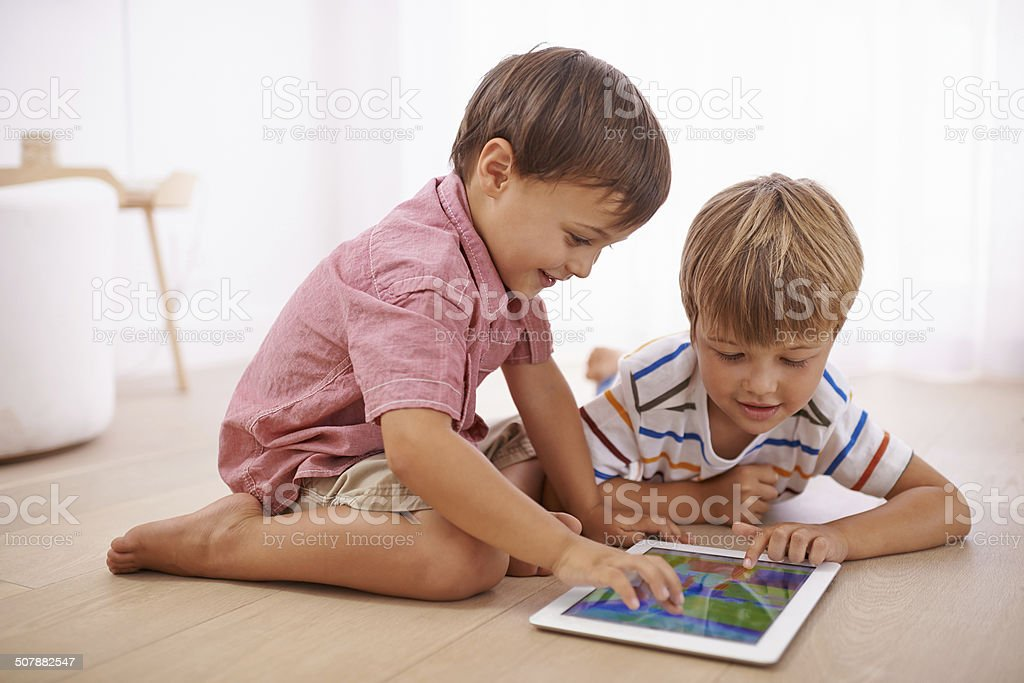 Let's crop some people out of our pics!!! Two young boys playing on a digital tablet on the floor at home Blond Hair Stock Photo