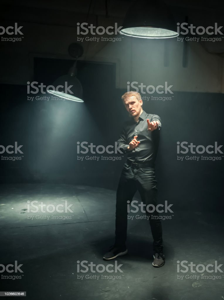 Handsome bearded man in black clothing dances the hip-hop moving his...