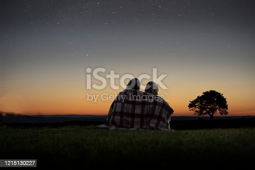 A mature couple sitting wrapped in a blanket looking at the night sky full of stars.