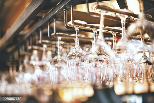 Wine glasses hanging over a bar rack. Golden brown background.