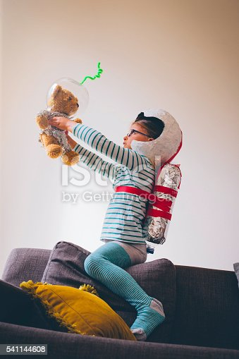 Little girl holding her teddybear, both dressed up as astronauts in homemade helmets, jetpack and spacesuit. The little girl is face to face with her teddy bear. She is in a living room at home.