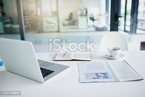Still life shot of a laptop and paperwork on a desk in an office