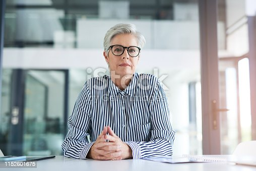 Portrait of an attractive mature businesswoman sitting at her office desk at work