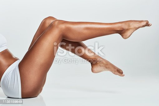 Cropped shot of a young woman's legs against a grey background