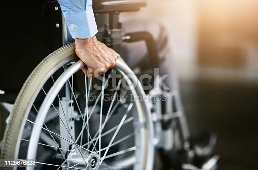 Closeup shot of an unrecognizable man sitting in a wheelchair