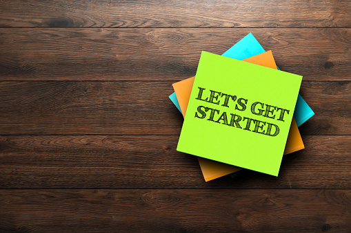 istock Let's Get Started, the phrase is written on multi-colored stickers, on a brown wooden background. Business concept, strategy, plan, planning. 956959350