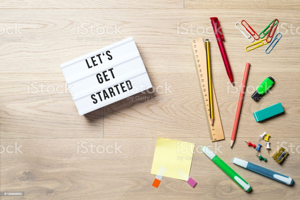Let's get started written on lightbox in office as flatlay stock photo