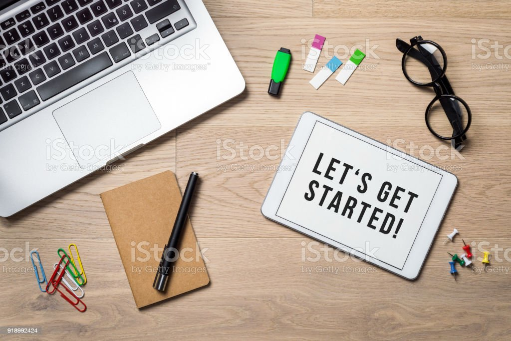 Let's get started written on tablet lying on desk as flatlay stock photo
