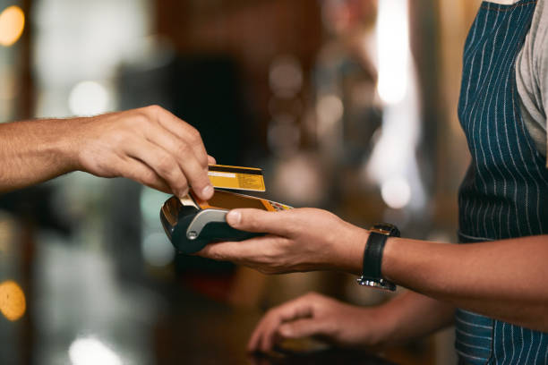 Let's get the payment over with Shot of two unrecognizable people making an exchange in payment with a credit card inside of a beer brewery during the day smart card stock pictures, royalty-free photos & images