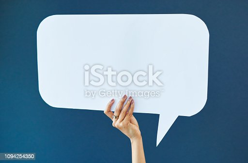 Studio shot of an unrecognizable woman holding up a sign against a blue background