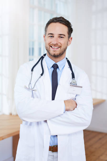 Let's get you better asap Portrait of a confident young doctor standing in his consulting room ASAP stock pictures, royalty-free photos & images