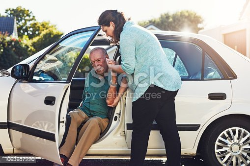 Cropped shot of a woman helping her senior father out of the car