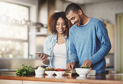 Shot of a happy young couple using a digital tablet while preparing a healthy meal together at home