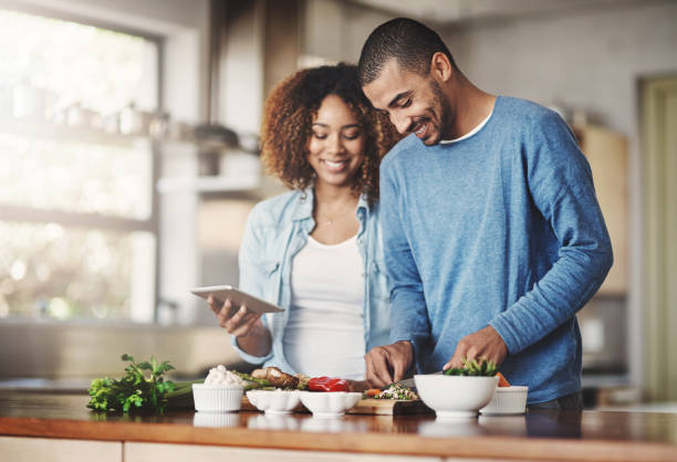Let's give this recipe a try Shot of a happy young couple using a digital tablet while preparing a healthy meal together at home preparing food stock pictures, royalty-free photos & images