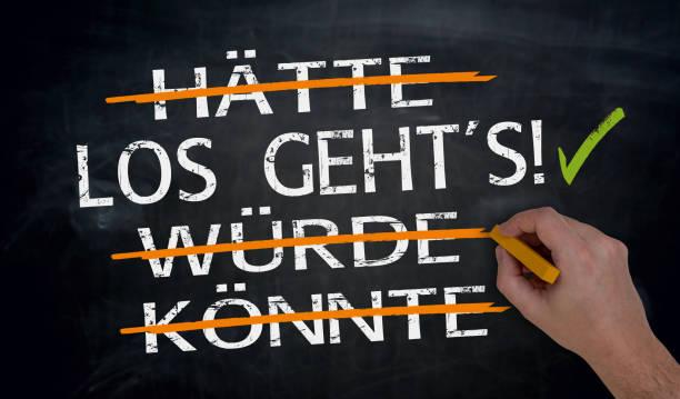 Los geht's, haette, wuerde, koennte (in german Let's go, could, should; would) written by hand on blackboard – Foto