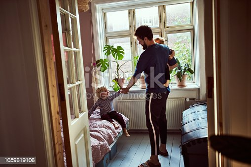 Full length shot of a young man trying to get his children ready in the morning