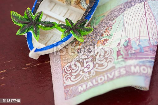 A tropical figure on 5 Maldivian Currency (Rufiyaa) both on wooden texture.