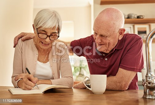 Shot of a senior woman making notes while talking to her husband