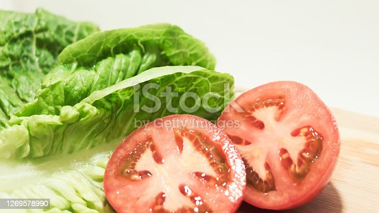 Close-up of fresh and organic lettuce leaves next to a tomato cut in a half on a wooden cutting table in a bright and white background