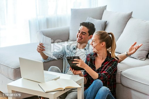 Photo of a happy couple doing finances at home. Photo of a cheerful loving young couple using a laptop and analyzing their finances with documents. Looking at papers. Happy couple at home paying bills with the laptop. Loving young couple using a laptop and analyzing their finances. Writing notes.