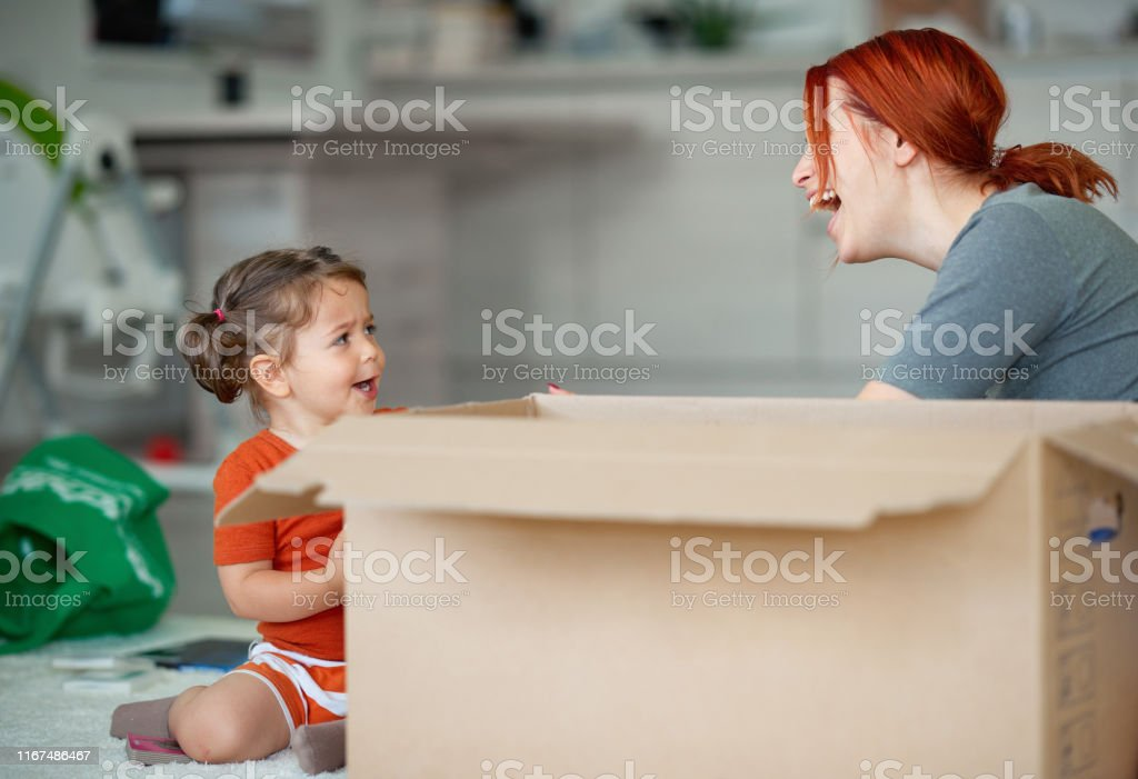 Mother with her daughter arranging clothes and enjoying it